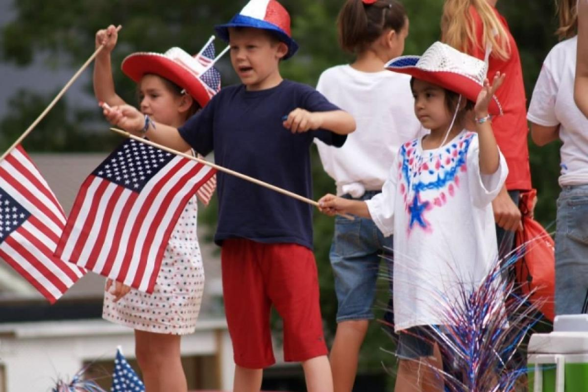 Children with American flags watching a parade